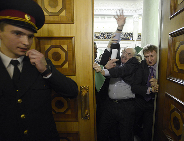 Members of parliament scuffle with colleagues who were elected from their party but later refused to join a faction, at the first session of newly-elected Ukrainian parliament in Kiev, December 12, 2012. (Photo by Andrew Kravchenko/Reuters)