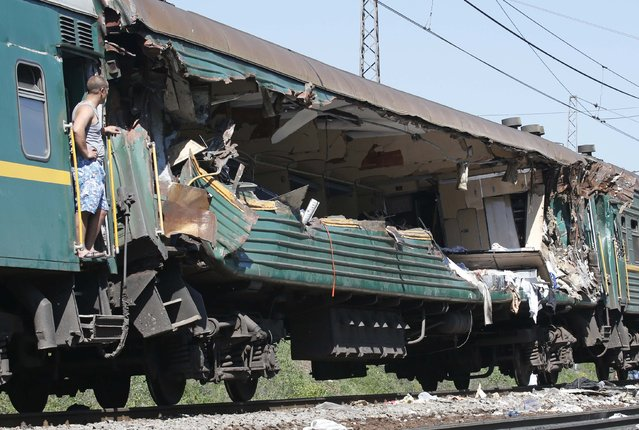 A man stands at a passenger train damaged in a collision with a freight train in Moscow region May 20, 2014. The passenger train on its way to Moldova collided with a freight train near Moscow on Tuesday, killing at least four people and injuring 15, a spokeswoman for Russia's Emergencies Ministry said. The reason for the collision, near the town of Naro-Fominsk 55 km (34 miles) southwest of Moscow, was not immediately clear. (Photo by Grigory Dukor/Reuters)