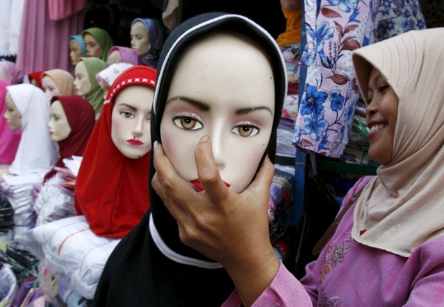 An Indonesian vendor fixes a headscarf on a mannequin at a market in Jakarta in this December 21, 2006 file photo. (Photo by Reuters/Beawiharta)