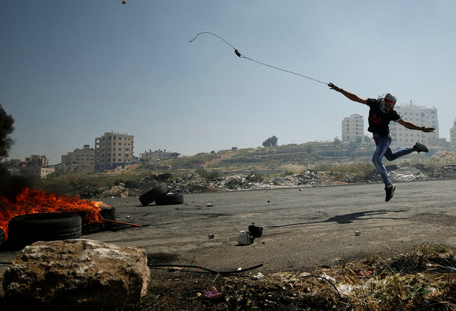 A Palestinian protester uses a sling to hurl stones towards Israeli troops during clashes at a protest in support of Palestinian prisoners on hunger strike in Israeli jails, near the Jewish settlement of Beit El, near the West Bank city of Ramallah May 11, 2017. (Photo by Mohamad Torokman/Reuters)