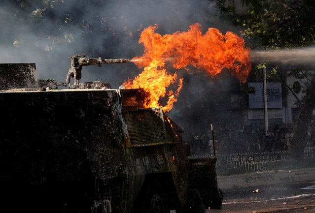 A riot police vehicle with flames uses its water cannon during an anti-government protests in Santiago, Chile on October 28, 2019. (Photo by Henry Romero/Reuters)