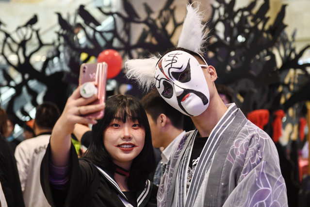 This photo taken on October 31, 2019 shows people in costumes taking a selfie during a Halloween event in Nanjing in China's eastern Jiangsu province. (Photo by AFP Photo/China Stringer Network)