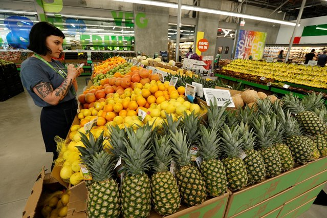 An employee checks prices of lemons at a 365 by Whole Foods Market grocery store ahead of its opening day in Los Angeles, U.S., May 24, 2016. (Photo by Mario Anzuoni/Reuters)