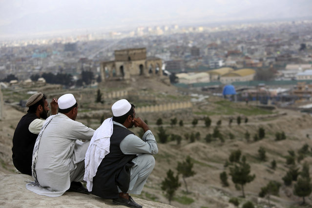 "In this March 27, 2017, file photo, men sit on the Nadir Khan hilltop overlooking Kabul, Afghanistan. As America's 16-year war in Afghanistan drags on, Russia is resurrecting its own interest in the ""graveyard of empires"". The jockeying includes engaging the Taliban and leading a new diplomatic effort to tackle Afghanistan's future, all while Washington leaves the world guessing on its strategy for ending the conflict. (Photo by Rahmat Gul/AP Photo)"