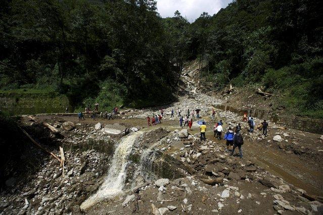 People walk along a blocked highway after a landslide at Lumle village in Kaski district July 30, 2015. (Photo by Navesh Chitrakar/Reuters)