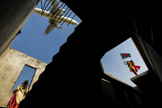 """Lets Keep Open all the Windows"". On the Victory Day of Bangladesh, 16 December, the local children who live near Runway are celebrating and waving flags while an aircraft is going to land in the airport. Photo taken from a staircase of a half-constructed building. Photo location: Dhaka, Bangladesh. (Photo and caption by Md Khalid Rayhan Shawon/National Geographic Photo Contest)"