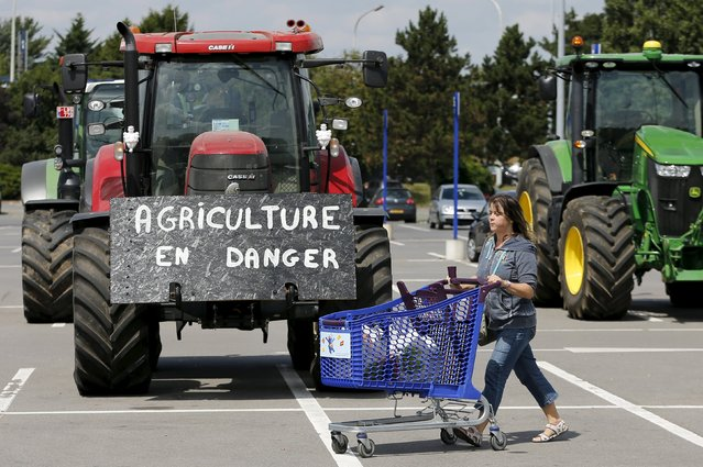 "A customer pushes a shopping trolley next to tractors as Belgian dairy farmers block the entrance of a Carrefour supermarket during a protest against low milk prices in Waterloo near Brussels, Belgium, July 31, 2015. The sign on the tractor reads ""Agriculture in danger"". (Photo by Francois Lenoir/Reuters)"