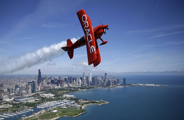 Aerobatic pilot Sean D. Tucker flies in the two-seat Oracle Extra airplane over downtown Chicago skyline, Wednesday, June 8, 2016. Tucker will perform before the start of of the America's Cup World Series racing on Saturday and Sunday. (Photo by Kiichiro Sato/AP Photo)
