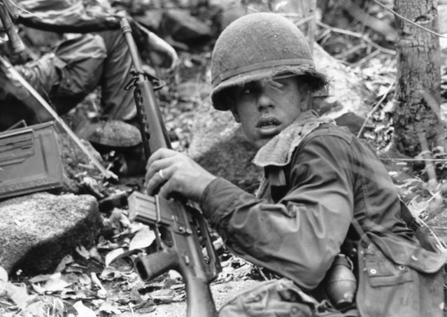 Seeing his first action since landing in Vietnam, a U.S. paratrooper of the 1st Battalion, 173rd Airborne, looks over his shoulder while leading his unit uphill against Viet Cong snipers near Vung Tau, May 26, 1965. The snipers eventually withdrew. (Photo by Horst Faas/AP Photo)
