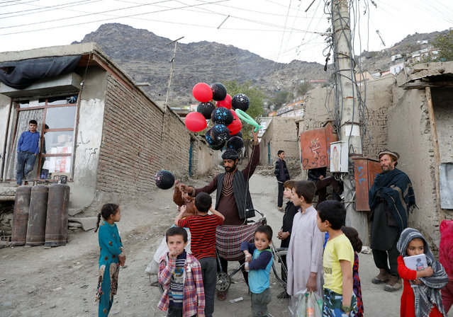 Children buy a balloon from a vendor in Kabul, Afghanistan on October 30, 2019. (Photo by Mohammad Ismail/Reuters)