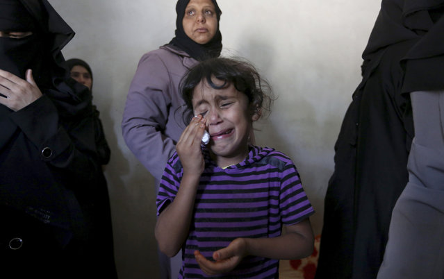 Asma weeps at the funeral of her brother, Gomha Abu Shalouf, 27, a member of the Ezz Al-Din Al Qassam Brigades, the military wing of Hamas, who was killed in an airstrike in Rafah, southern Gaza Strip on Monday, July 7, 2014. The Islamic militant group Hamas that rules Gaza vowed revenge on Israel for the death of several of its members killed in an airstrike early Monday morning in the deadliest exchange of fire since the latest round of attacks began weeks ago. (Photo by Hatem Moussa/AP Photo)