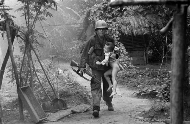 A U.S. infantryman from A Company, 1st Battalion, 16th Infantry  carries a crying child from Cam Xe village after dropping a phosphorous grenade into a bunker cleared of civilians during an operation near the Michelin rubber plantation northwest of Saigon, August 22, 1966
