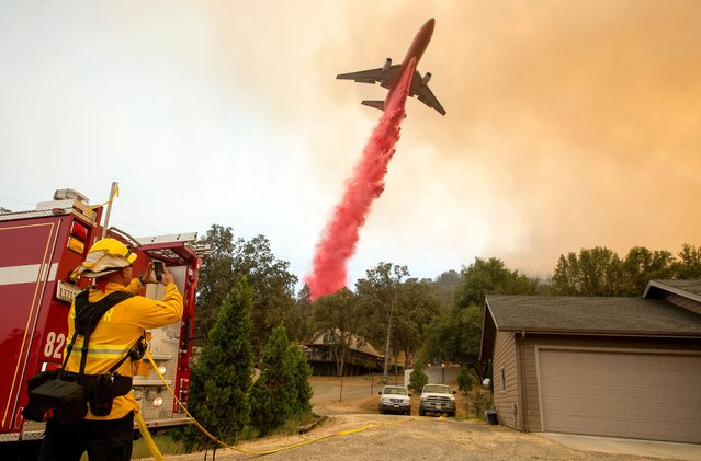 An air tanker drops fire retardant on flames as firefighters continue to battle against the Detwiler fire in Mariposa, California on July 19, 2017. The Detwiler fire is currently at 7 percent containment and has burned more than 45,000 acres and destroyed eight structures. (Photo by Josh Edelson/AFP Photo)