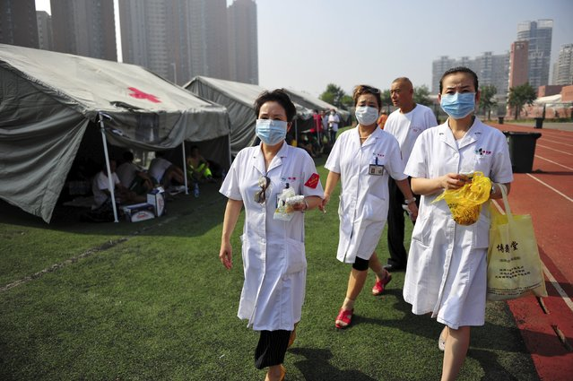 Medical volunteers walk past tents set up at the playground of a primary school as temporary shelters for victims after explosions at Binhai new district in Tianjin, China, August 13, 2015. (Photo by Reuters/Stringer)