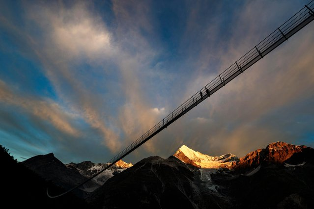 """A couple walks on the """"Europabruecke"""", supposed to be the world's longest pedestrian suspension bridge with a length of 494m, prior to the official inauguration of the construction in Randa, Switzerland, on Saturday, July 29, 2017. (Photo by Valentin Flauraud/Keystone via AP Photo)"""