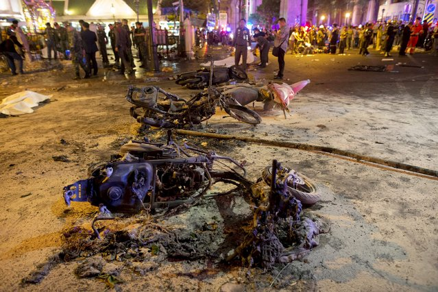 Wreckage of motorcycles are seen as security forces and emergency workers gather at the scene of a blast in central Bangkok August 17, 2015. A bomb on a motorcycle exploded on Monday just outside a Hindu shrine in the centre of the Thai capital, killing at least 12 people, police and a rescue worker said. (Photo by Athit Perawongmetha/Reuters)