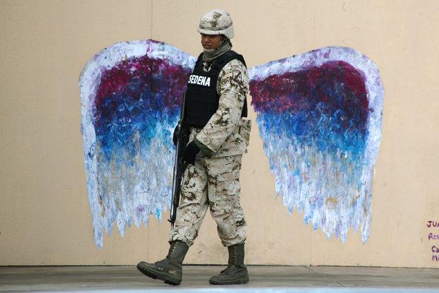 A soldier walks past graffiti depicting angel wings by artist Colette Miller in Ciudad Juarez on March 18, 2015. (Photo by Jose Luis Gonzalez/Reuters)