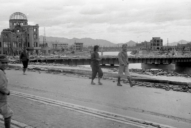 People walk over Aioi Bridge as the gutted Hiroshima Prefectural Industrial Promotion Hall (L), currently known as Atomic Bomb Dome or A-Bomb Dome, is seen in the background after the atomic bombing of Hiroshima, Japan, on August 6, 1945, in this handout photo taken by Shigeo Hayashi in October 1945 and released by Hiroshima Peace Memorial Museum. (Photo by Shigeo Hayashi/Reuters/Hiroshima Peace Memorial Museum)