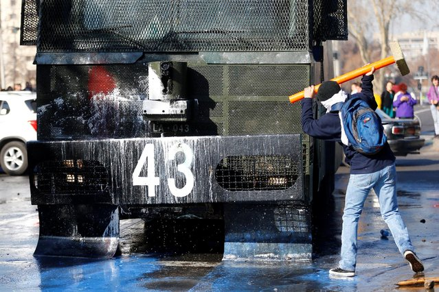 A demonstrator prepares to hit a riot police vehicle during an unauthorized march called by the Chilean student federations to protest against government's education reform, in Santiago, Chile July 5, 2016. (Photo by Ivan Alvarado/Reuters)