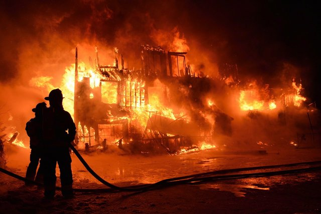 Fire engulfs a seniors residence in L'Isle-Verte, Que., early Thursday, Jan.23, 2014. A multimillion-dollar lawsuit has been filed against the Quebec town where 32 people died in a fire at a seniors' home last January. (Photo by Frances Drouin/The Canadian Press)