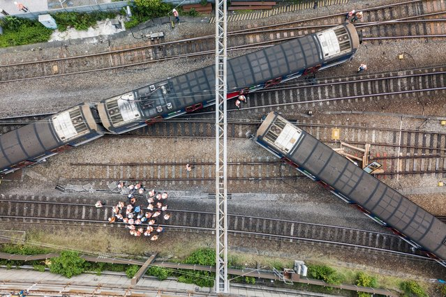 This aerial picture shows rescue workers standing on a railway track near a passenger train, after it derailed during rush hour outside Hung Hom station on the Kowloon side of Hong Kong on September 17, 2019. A passenger train derailed during the morning rush hour in Hong Kong on September 17 leaving three people injured, authorities said. (Photo by Anthony Wallace/AFP Photo)
