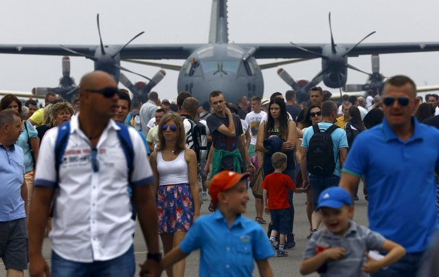 People walk at the static plane exhibition during the Radom Air Show at an airport in Radom, Poland August 23, 2015. (Photo by Kacper Pempel/Reuters)