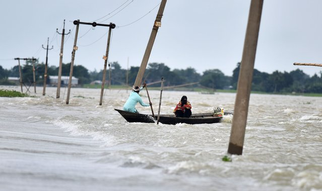 Indian villagers paddle a boat along a submerged road in the flood-affected Ashighar village in the northeastern state of Assam on July 5, 2016. (Photo by Biju Boro/AFP Photo)