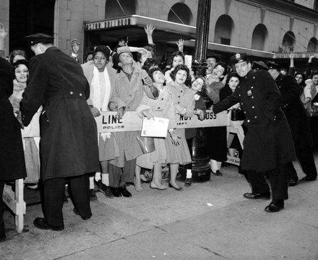 "New York City police attempt to restrain part of a group of thousands of ""Rock N' Roll"" enthusiasts as they wait on west 44th street in New York on February 21, 1957, for entrance to the Paramount Theater to see a movie and stage show. A glass panel was broken in an adjacent store and two girls sustained leg injuries. Some 50 policemen were called to the area and west 45th between Broadway and Eighth Avenue was closed to traffic. (Photo by AP Photo)"