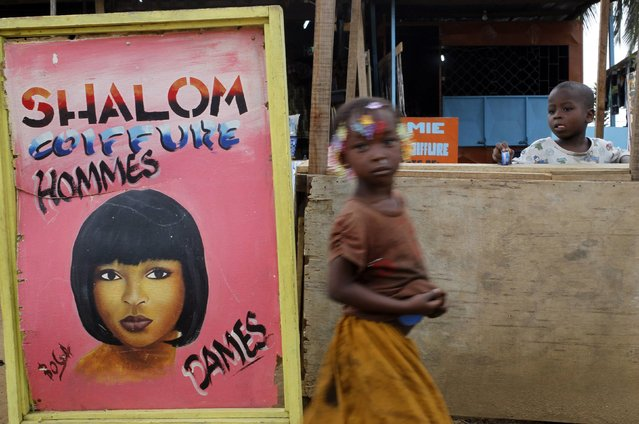 """Children play near a hairdressing salon sign at """"Colombie"""" (Colombia), a shanty town, in Abidjan, in this file picture taken August 5, 2014. While still largely based in the informal economy, the African haircare business has become a multi-billion dollar industry that stretches to China and India and has drawn global giants such as L'Oreal and Unilever. Hairdressers are a fixture of markets and taxi ranks across Africa, reflecting both the continent's rising incomes and demand from hair-conscious women. (Photo by Luc Gnago/Reuters)"""