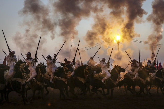 In this Thursday, August 17, 2017 photo, horse riders fire their gunpowder filled rifles as they take part in Tabourida, a traditional horsemanship show also known as Fantasia, in Mansouria, near Casablanca, Morocco. Thousands gathered recently in Mansouria, a small town south of the capital Rabat, to attend one of the oldest festivals in Morocco. Nineteen horse troupes came from different parts of the kingdom to celebrate a three-day event that blends courage, skill and tradition. (Photo by Mosa'ab Elshamy/AP Photo)