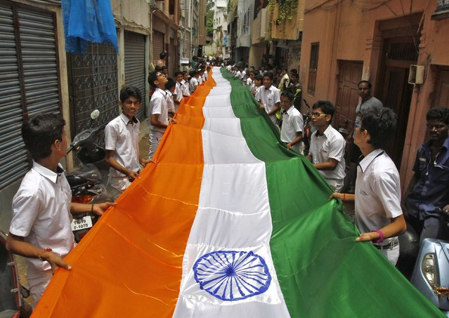 School students hold a 200-meter-long Indian national flag during India's Independence Day celebrations in the southern Indian city of Chennai August 13, 2014. India commemorates its Independence Day on August 15. (Photo by Reuters/Babu)