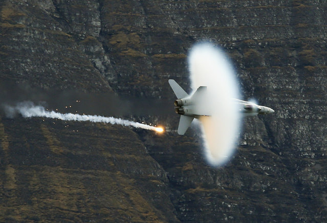 A Swiss Air Force F18 fighter jet releases flares during a flight demonstration of the Swiss Air Force over the Axalp in the Bernese Oberland, Switzerland October 11, 2012. (Photo by Pascal Lauener/Reuters)