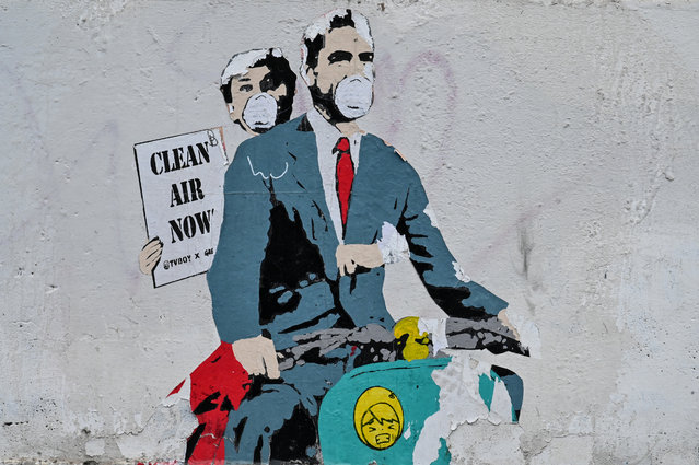 """A mural by street artist """"TV Boy"""" depicting a famous film """"Roman Holiday"""" with Gregory Peck and Audrey Hepburn as she  holding a banner reading """"Clear Air Now"""" is displayed on a wall near ancient Colosseum, in central Rome on March 14, 2020, during the COVID-19 outbreak caused by the novel coronavirus. (Photo by Andreas Solaro/AFP Photo)"""