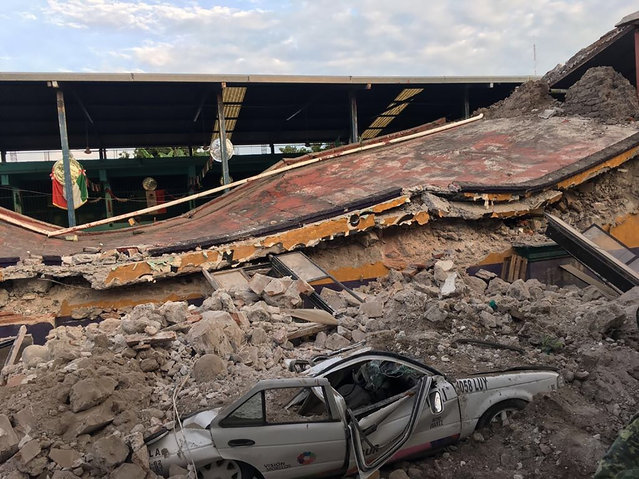A car sits crushed, engulfed in a pile of rubble from a building felled by a 7.1 earthquake, in Jojutla, Morelos state, Mexico, Tuesday, September 19, 2017. (Photo by Carlos Rodriguez/AP Photo)