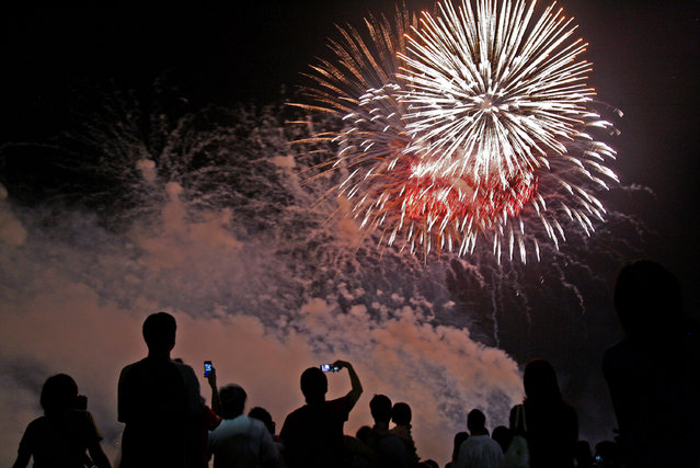 People are silhouetted against a fireworks display by China's Lidu Fireworks company, during the annual fireworks festival, Singapore, Saturday, August 18, 2007. (Photo by Wong Maye-E/AP Photo)