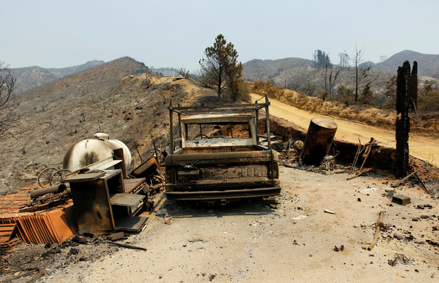 A burned out vehicle is seen at the site of a destroyed house after the Soberanes Fire burned through the Palo Colorado area, north of Big Sur, California, July 31, 2016. (Photo by Michael Fiala/Reuters)