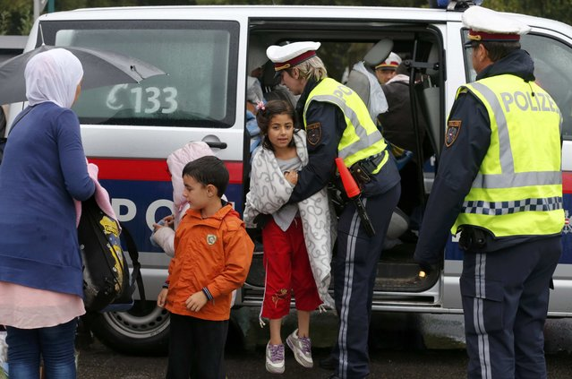 Austrian Police helps migrants as they arrive at the train station of Nickelsdorf, Austria to board a train to Germany, September 5, 2015. (Photo by Heinz-Peter Bader/Reuters)