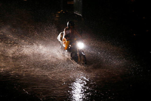 A motorcyclist wades through a waterlogged street during rains in New Delhi, India August 1, 2016. (Photo by Adnan Abidi/Reuters)