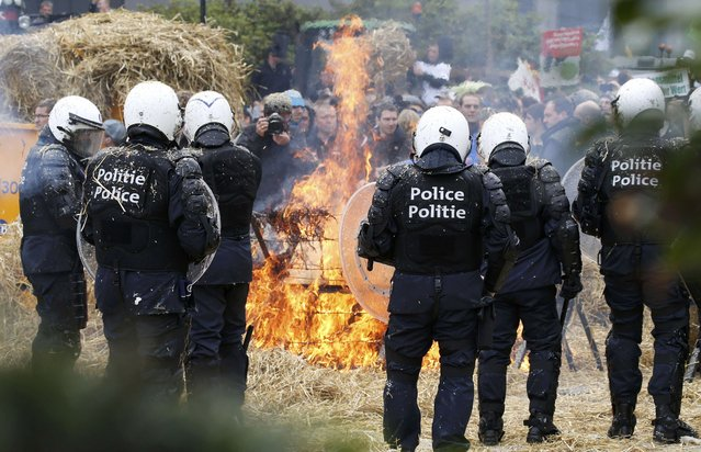 Belgian riot police officers stand guard as demonstrators burn hay while farmers and dairy farmers from all over Europe take part in a demonstration outside an European Union farm ministers emergency meeting at the EU Council headquarters in Brussels, Belgium, September 7, 2015. (Photo by Jacky Naegelen/Reuters)