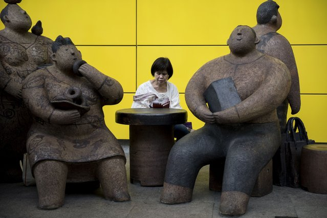 A woman reads on her mobile phone next to sculptures by artist Rosanna Li Wei-han outside an MTR station in Hong Kong on September 6, 2014. Hong Kong's economy in 2014 is expected to expand at its fastest pace in three years, according to government estimations, with a forecasted growth of between three and four percent, up from 2.9 percent in 2013. (Photo by Alex Ogle/AFP Photo)