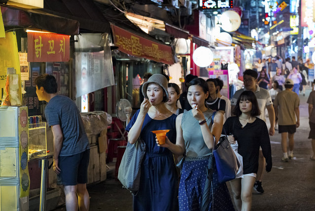 Young people walk an alley in Hongdae area on July 29, 2015 in Seoul, South Korea. The Hongdae area is a region around Hongik University in Seoul, South Korea. Hongdae is an abbreviation of 'Hong'ik 'Dae'hakyo, Hongik University. Hongdae is know for entertainment, food and beverage, arts, shopping and clubs for indie music to dance floor for South Korean youngsters. (Photo by Shin Woong-jae/The Washington Post)