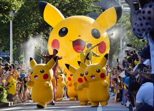 "Performers dressed as Pikachu, the popular animation Pokemon series character, perform in the Pikachu parade in Yokohama on August 7, 2016. Some 50 life-size Pikachu characters, the most famous from the Pokemon game, marched along the city's waterfront street as visitors took mobile phone pictures and videos of them in scorching sunshine. Some participants said they attended the event to search for rare characters of Pokemon – a word short for ""pocket monster"" – for the megahit smartphone app, which was launched in several countries around the world last month. (Photo by Kazuhiro Nogi/AFP Photo)"
