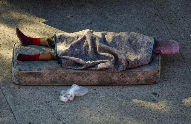 A man sleeps in a mattress in the middle of a street of 1-11-14 slum at San Lorenzo's Pedro Bidegain Stadium on May 18, 2020 in Buenos Aires, Argentina. According to official reports, poor settlements represent 30% of the positive cases in Buenos Aires City. (Photo by Amilcar Orfali/Getty Images)