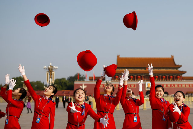 Ushers throw their hats in the air as they pose for photographers at the Tiananmen Square before the start of the closing session of the 19th National Congress of the Communist Party of China, in Beijing, China October 24, 2017. (Photo by Thomas Peter/Reuters)