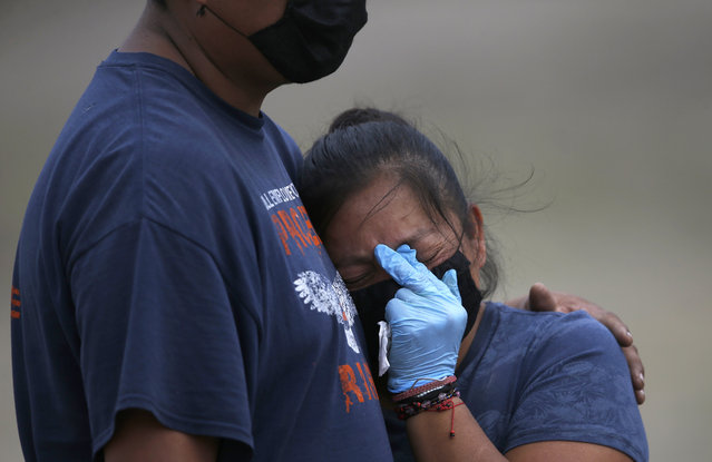 A couple wearing masks and gloves to protect themselves from the new coronavirus mourn during the burial of their loved one at the newly constructed Valle de Chalco Municipal Cemetery, built to accommodate the rise in deaths amid the new coronavirus pandemic, on the outskirts of Mexico City, Thursday, May 21, 2020. (Photo by Marco Ugarte/AP Photo)
