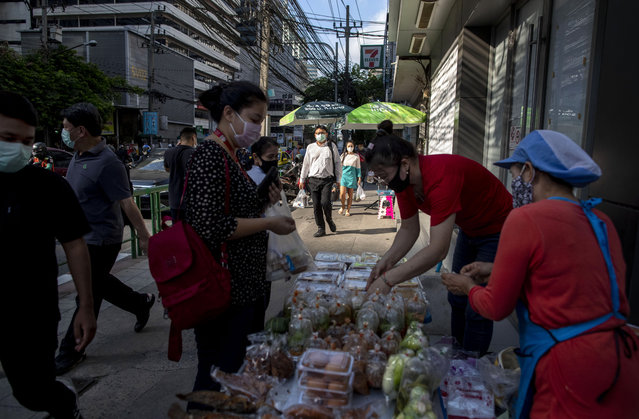 Office workers wearing face masks buy cooked food from street venders in Bangkok, Thailand, Wednesday, May 13, 2020. (Photo by Gemunu Amarasinghe/AP Photo)