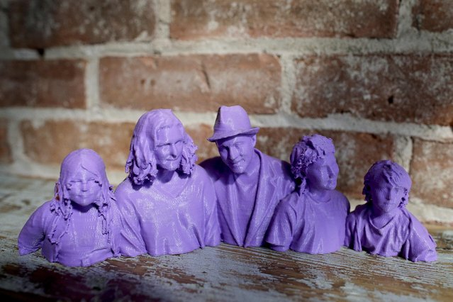 In this August 14, 2014 photo, a plastic bust statue of Kevin Micelli, center, and his family, made by a 3-D scanner and printer, sits on a shelf inside Micelli's coffee shop in New York. Micelli purchased the 3-D scanning and printing services at the Cubo toy store next door to his shop. With the old studio portrait supplanted by the selfie, 3-D scanning services provide a new reason for people to go to a store and stand stock-still in front of a camera. (Photo by Julie Jacobson/AP Photo)