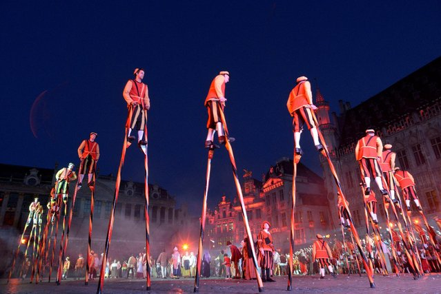 Stilt walkers wearing medieval costumes perform during an annual Renaissance pageant, the Ommegang parade, which commemorates the 16th century arrival of Habsburg Emperor Charles V, on Brussels Grand Place, Belgium, July 3, 2014. (Photo by Eric Vidal/Reuters)