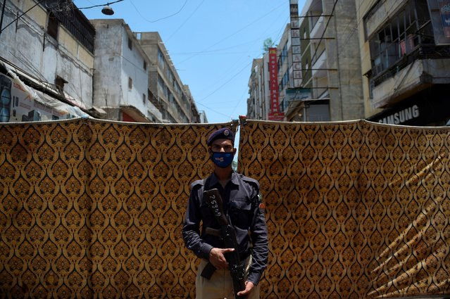 A policeman stands guard in a blocked street which was sealed by the authorities in Karachi on June 20, 2020, after the COVID-19 coronavirus cases continue to rise. (Photo by Rizwan Tabassum/AFP Photo)