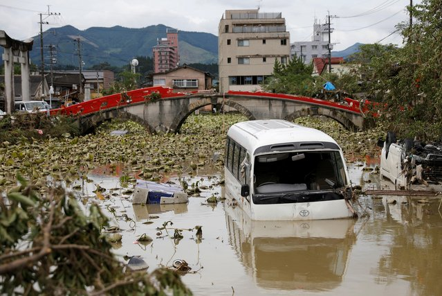 A broken bridge is seen in the back, as an overturned vehicle and a partially submerged bus are pictured in floodwaters caused by torrential rain in Hitoyoshi, Kumamoto Prefecture, southwestern Japan, July 8, 2020. (Photo by Kim Kyung-Hoon/Reuters)